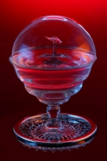 Water drop collision in a glass under a bubble